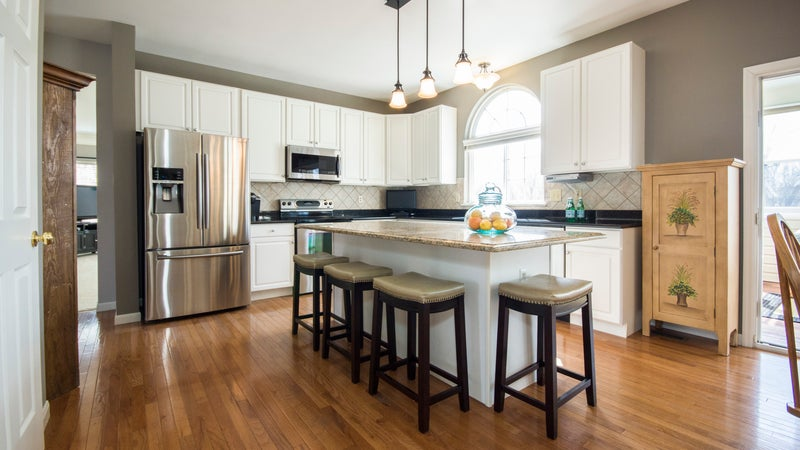 A kitchen with an island, barstools, and hardwood floors