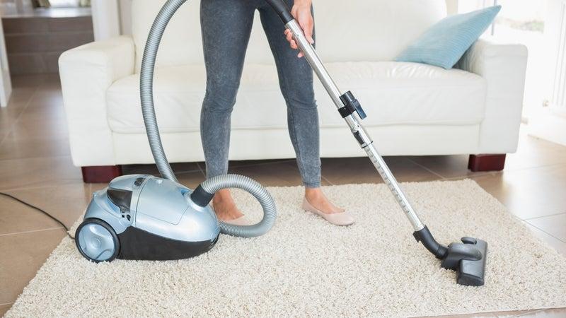 Woman hoovering rug in living room