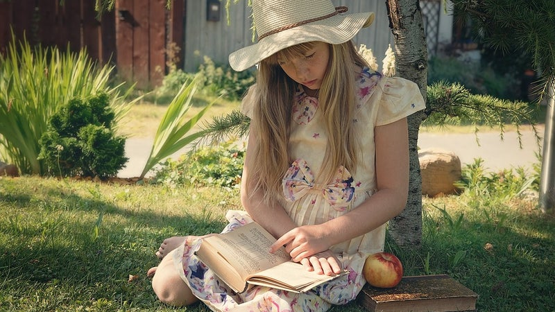 young girl sitting outside with a book